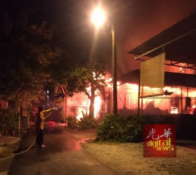 排屋火灾后,邻居帮忙救火。