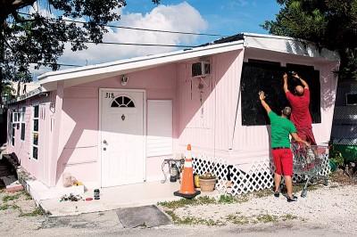 """佛罗里达州居民为家园钉上木板防风。预料""""艾玛""""吹袭美国后,整个""""艾玛""""吹袭带来的损失将逾1200亿美元(约5040亿令吉)。(法新社照片)"""