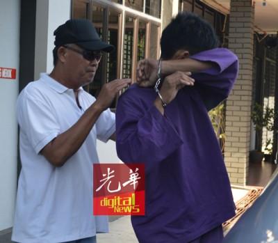 嫌犯被押送离开法庭时以手遮脸避开摄影镜头。