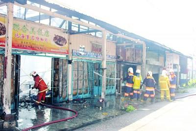 排拯员在现场向店屋灌水,防止再度起火,看得出店屋内浓烟未散。