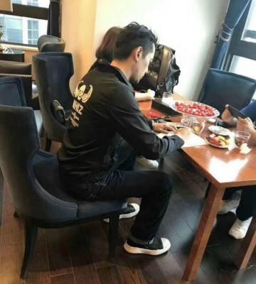 胡歌坐在办公桌前,右手拿笔疑似在签文件合同。