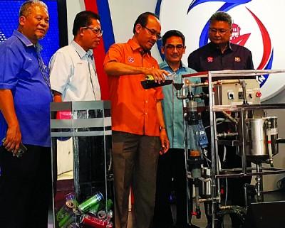 莫哈末嘉益士(左3)将使用后的食油倒入机器中,上述机器能将再循环食用油提炼成生物柴油。