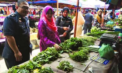 沙哈宁(中)在阿末等陪同下,检查农集市场统制货价格。