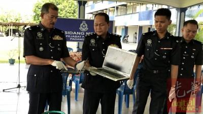诺依里斯(左)跟一多警官示出派出所所起获到的手提电脑等物品。