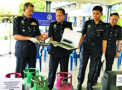 诺依里斯(左)以及一多警官示出派出所所起获到的手提电脑等物品。