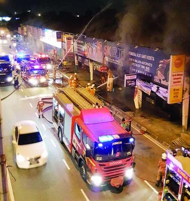 北海市区4单位双层楼经营汽车零件毗邻店铺着火,消拯员正急救。