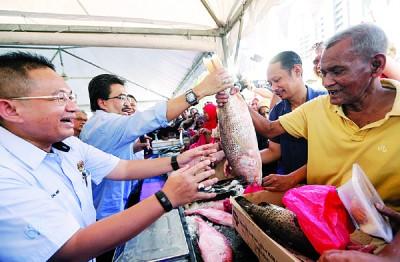 大马渔业发展局也提供新鲜便宜的鱼类,在活动中,佐哈里(左2)亲自扮演鱼贩角色,高举一条鱼卖给人民组屋居民。左为依莫希占。