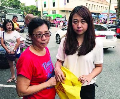 张美英(左)向廖彩彤投诉被割破的环保袋。