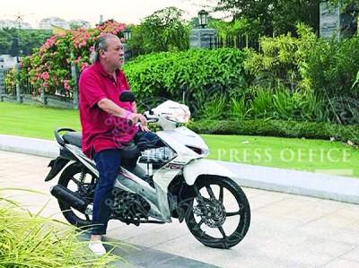 陛下骑摩托车巡视王宫周围卫生。