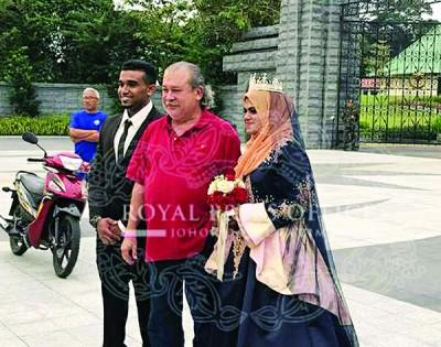 一对正在王宫外拍摄婚纱照的印裔新人把握机会,与陛下合影。