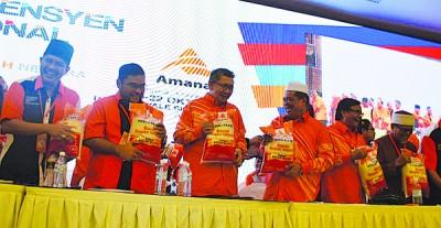 莫哈末沙布(左4)与党领袖手握印有党标志的一包包白米。
