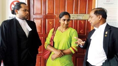 古拉律师(右)与女教师乌玛(中)讲解。