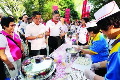 洪文兴(左2起)和郑金财观看参赛者如何制作糕点。