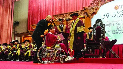 韩庆中(坐轮椅者)从沙烈(前排右)手中接获工大化学教育硕士文凭。