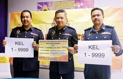 依斯玛苏海米(中)与注册单位主任朱卡纳(右)及公关依斯干达(左)展示「KEL 1」至「KEL 9999」的车牌,即日起已公开让民众下标预定。