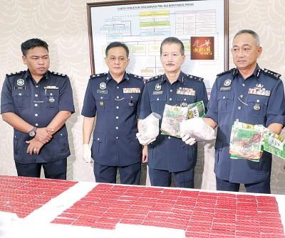 哈斯南(右)在颜天记(右2)展示警方起的毒品。