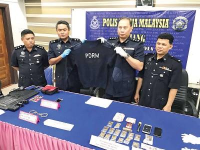 扎菲尔(右2)展示在其中一名假警的住家中起获的假外套。