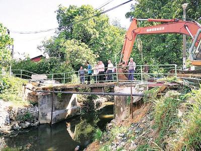 黄汉伟等人巡视安乐村桥。