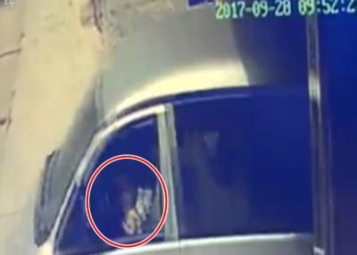 肇事轿车溜前时,男童(红圈示)坐在驾驶席上。