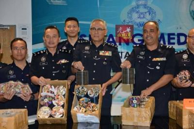 阿克里沙尼(左4)向媒体展示警方起获的光碟。