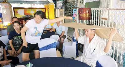 68岁死者张妹的女儿和儿子练淼新展示死者生前自制遮阳的纸皮。