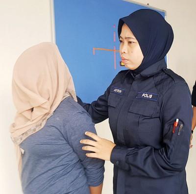 女被告被押出法庭时,用头巾遮盖脸部避开媒体镜头。