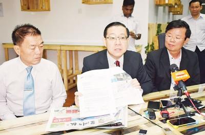 林冠英(中)出示张盛闻支持吉打培才小学迁至威省峇冬丁宜的信函,旁为林峰成(左)及曹观友。