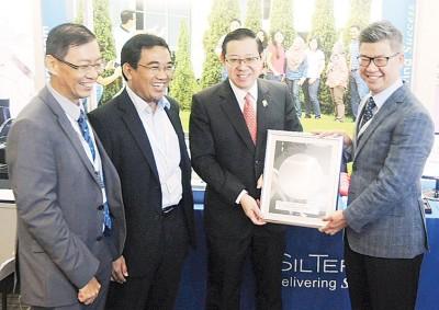 商矽佳股份有限公司台湾分公司执行副总裁刘一龙(右一)赠送纪念品予槟首长林冠英,左一为电子、电器、工程协会槟州分会财政林志荣。