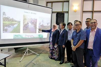 """槟岛市长拿督麦慕娜(左1)在槟岛市政厅秘书尤端祥(左2)和一众组织代表陪同下,介绍""""2018年城市骑行""""移师浮罗山背的绿色路线。"""