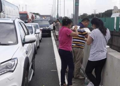 部分自驾者早有准备,在公路上吃饭盒。