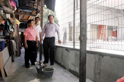 黄伟益(右)向媒体指出,发展商在住宅区之间兴建防水墙,避免在施工期间水源流向住宅区。