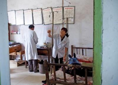 万兆民同夫人凡凤玲当简陋的诊治室为患童看。