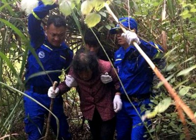 救援人员在山上寻获罗老太,将她带下山。