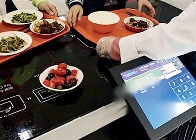 每个盘子底部均装有晶片,学生结帐时将托盘放在结算区即可显示用餐价格。