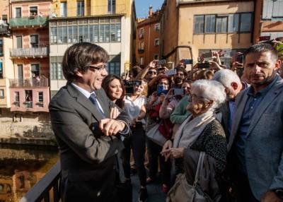 普伊格登莫尼特(左)回到家乡希罗纳,满面笑容和居民互动。(法新社照片)