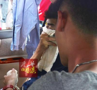 袁铬文的父亲在车内用手帕捂住脸。