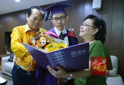 林永华(左)、翁菁镁(右)与林志伟分享戴四方帽的喜悦。