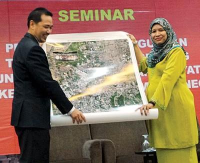 大马遥感系统机构总监阿兹里卡玛(左)赠送遥感系统观测的卫星图给予州行政议员诺莎比娜。