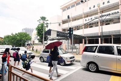 学校门前斑马线周围没有交通告示牌,学生家长战战兢兢过马路。