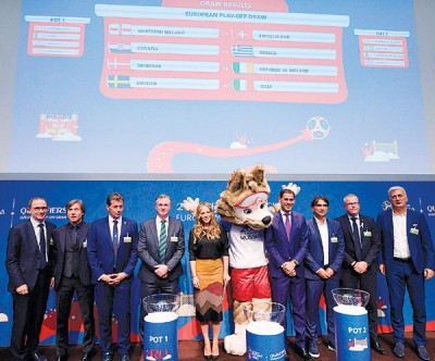 欧洲区附加赛抽签结果揭晓后,各队主帅在台上与2018年俄罗斯世界杯吉祥物合照。