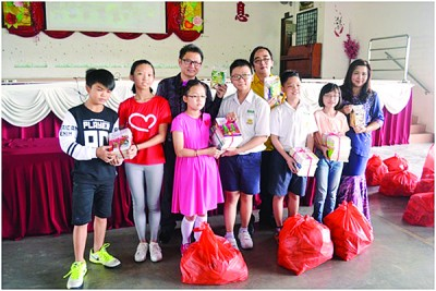 李凌篆(后排左起)、叶伟健副校长和邬绮清校长颁发儿童节恩物给各班的学生代表。
