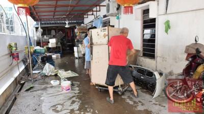 陈先生和家人忙着搬动损坏的冰箱,其住家一片凌乱。