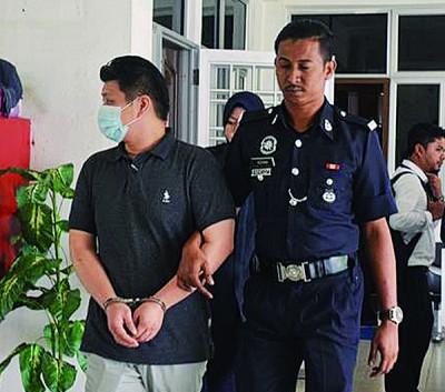 廖新传(左)被庭警押离法庭,送往马六甲监狱监禁1天。