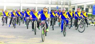 祖基菲里(中)与玻州警官骑自行车。前排右2为阿兹斯曼。