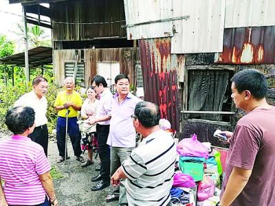 林峰成(左二),张瑞丰(右三)与发展商代表(右)及林操峇(左三)对话,罗伟鹏(右四)将州政府廉价屋申请表格交给林素真(左四)。