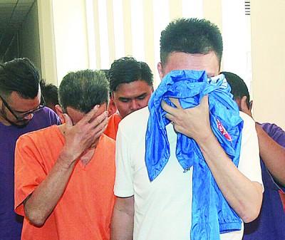 涉嫌攻击执法人员的嫌犯(右),上庭时以衣服掩盖颜面。