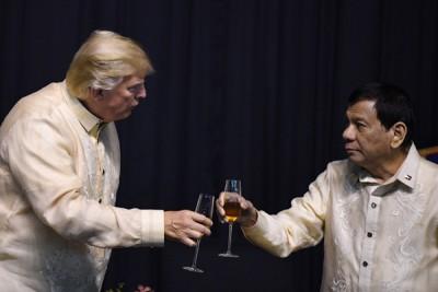 特朗普(左)跟遵循泰特(右)碰杯。(法新社照片)