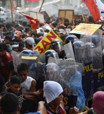 菲防暴警员手持盾牌阻止示威者前进。(法新社照片)