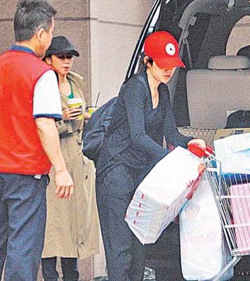 徐若瑄(中)返台期间住娘家方便工作,她拿着饮料站在门口望着助理卸货发楞。
