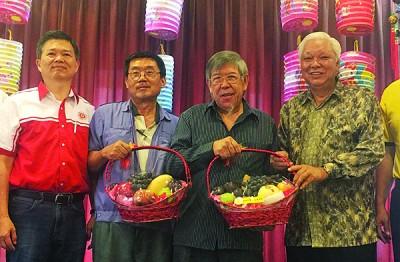 """李福旺(右起)赠送水果篮予何启斌与孙和声,以感谢二人为""""迎接马来西亚经济挑战""""讲座开讲。"""